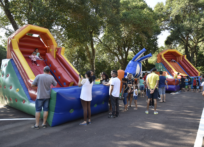 Crianças brincam em brinquedos infláveis enquanto pais observam