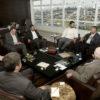 Sala de reuniões com pessoas sentadas em circulo e a vista de Jundiaí ao fundo