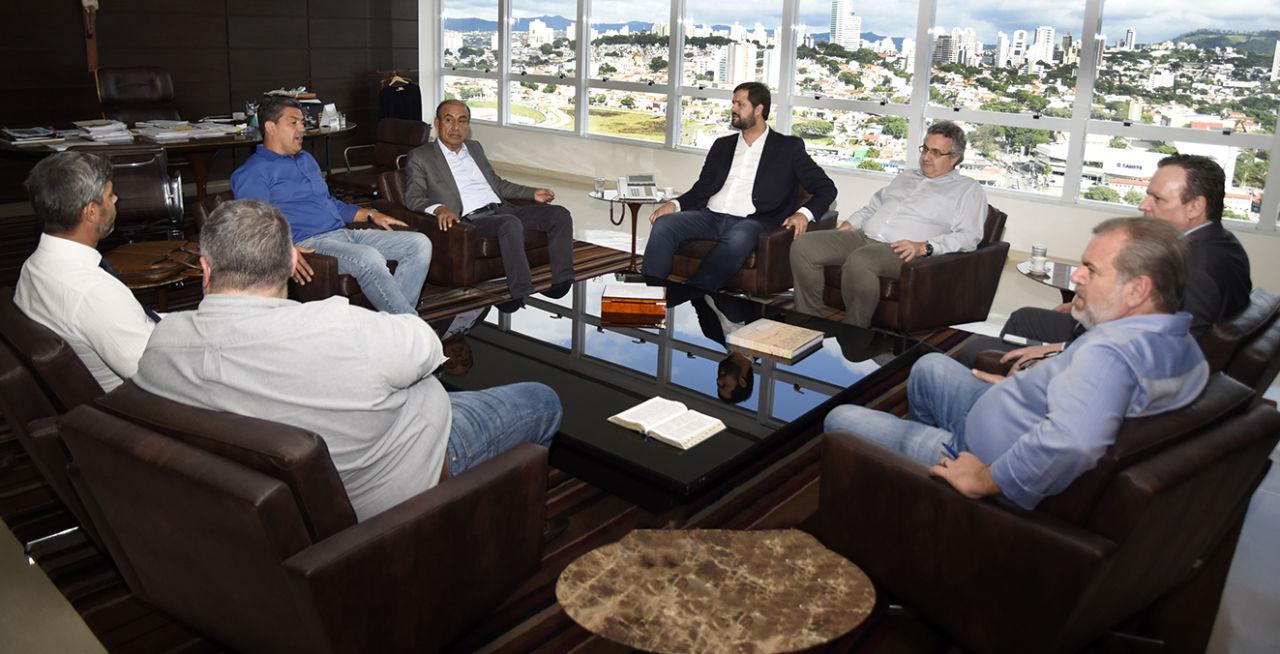 Foto da sala de trabalho do prefeito, com representantes da comitiva e gestores da Prefeitura sentados e panorama de Jundiaí visto da janela