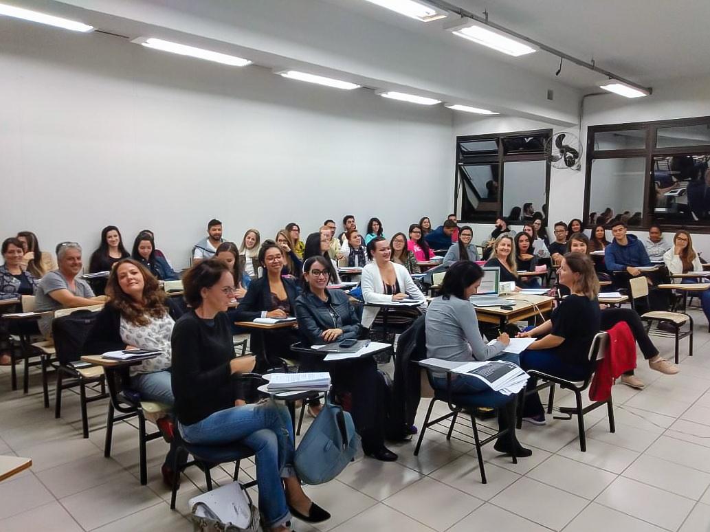 Sala de aula com alunos sentados assistindo à plaestra