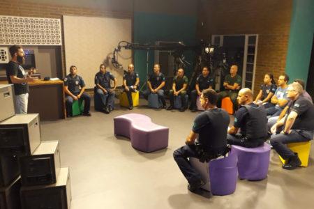 Guardas municipais sentados em círculo, durante aula em estúdio