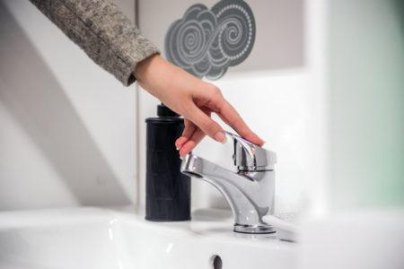 Mão fechando uma torneira