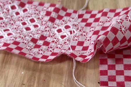 Foto de bordado em tecido xadrez nas cores branco e vermelho