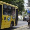 Mulher em ponto enquanto ônibus para