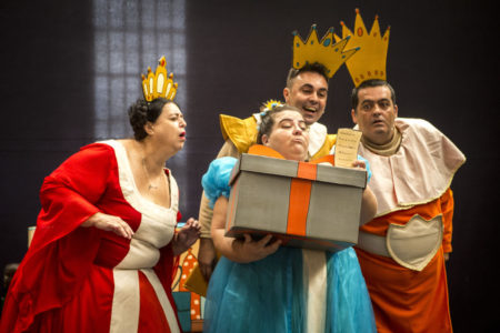 Atores fantasiados com roupas coloridas de realeza e atriz que representa a princesa Isabola recebe uma caixa de presente
