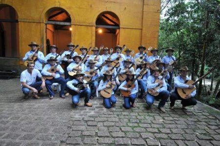 Foto posada dos integrantes da orquestra com seus instrumentos