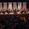 Músicos da orquestra se apresentando no palco do Polytheama com plateia