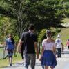 Pessoas caminhando na pista de pedestres do Parque da Cidade, com paisagem e árvores