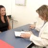 Médica faz atendimento à mulher em consultório