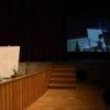 Artista pinta em tela, enquanto assiste à performance sobre o palco do Polytheama