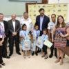 Em foto posada, prefeito, participantes e crianças com os kits