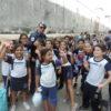 Guarda municipal posa para foto em meio a crianças uniformizadas