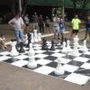 Crianças e adultos jogam xadrez em tabuleiro com tamanho humano