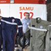 Funcionários seguram os dois novos modelos de uniformes (macacões)