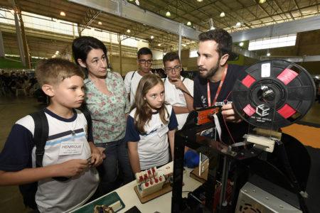 Alunos da rede municipal com uniforme, professora e outros estudantes assistem à explicação de guru do FAB LAB sobre o funcionamento da impressora 3D do laboratório