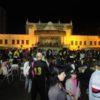 Foto noturna da Praça do Coreto, com multidão e fundo da Catedral iluminado