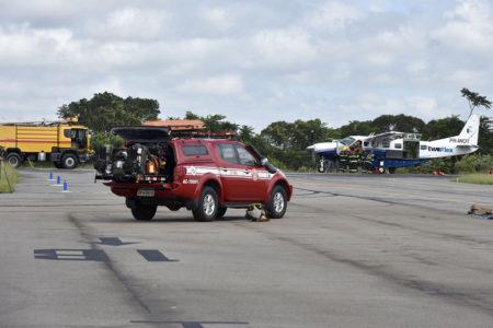 Carro do Corpo de Bombeiros com avião usado para simulação ao fundo
