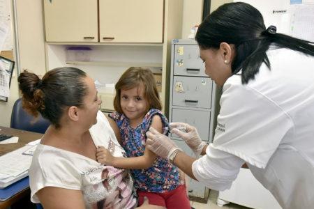 Enfermeira aplica vacina em menina que está no colo da mãe