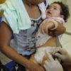 Mão segura criança no colo para tomar vacina
