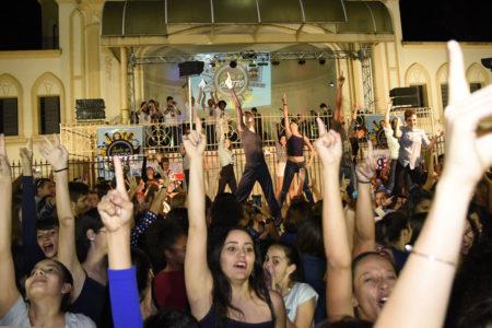 Foto noturna na Praça do Coreto, com a Matriz ao fundo e bailarinos em intervenção de flashmob com as mãos para o alto