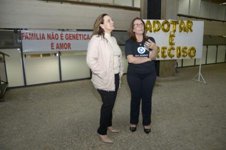 """Gestora da UGADS e representante do GAA em frente às placas de """"Família não é genética.... é amor"""" e """"Adotar é Preciso"""""""
