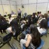Alunos sentados em cadeira com palestrantes à frente, de pé