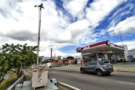 Foto de aparelho na calçada e carro passando na rua