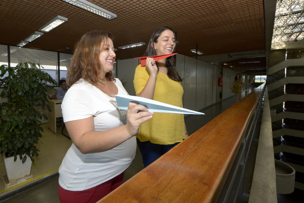 Duas mulheres gestantes no parapeito do Paço Municipal, segurando seus aviõezinhos antes do lançamento