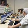 Três pessoas sentadas em frente a computadores enquanto professora está à frente