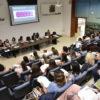 Pessoas sentadas em auditório enquanto pessoas, sentadas à mesa, fazem apresentação
