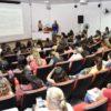 Auditório com as cadeiras ocupadas e duas palestrantes à frente