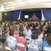 Pavilhão interno do Parque da Uva, com pessoas sentadas, assistindo a uma palestra no palco