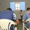 Roda de adolescentes não identificados assistem a palestra na garagem da TVTEC