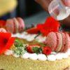 Foto de torta com macarrons rosas em cima e açúcar cristal sendo colocado por cima