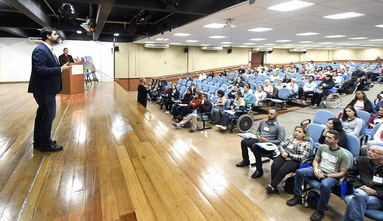 Prefeito em cima do palco falando para os participantes da Conferência