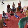 Em um tapete vermelho, crianças e adultos estão sentados no chão e em pufes quadrados; à frente deles, porém de costas para quem vê a imagem, estão duas mulheres gesticulando, contando uma história-
