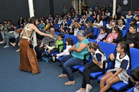Em um auditório amplo e cheio de adultos e crianças sentados, uma mulher mostra o fantoche de um cachorro a uma criança sentada na primeira fila