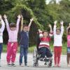 Crianças alinhadas posando com a foto com as mãos pra cima