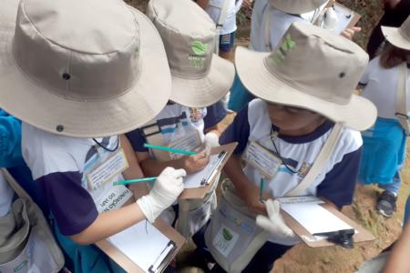 Estudantes com chapéus e segurando caneta e prancheta e fazem anotações