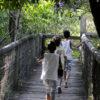 Três crianças caminham sobre ponte de madeira