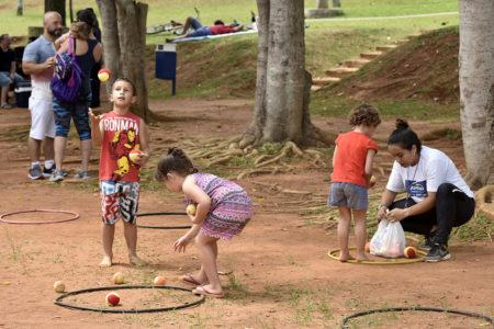 Três crianças brincando de bolas e bambolês, sob árvores e com a supervisão de monitora