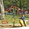 Três crianças brincando em gira-gira de cadeiras e cavalinhos de montar