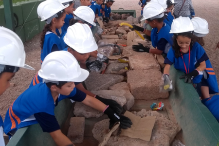 Crianças com capacetes brancos separando lixos recicláveis