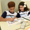 Aluno escreve em livro enquanto a colega olha