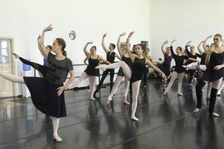 Bailarina Ana Botafogo com bailarinas acompanhando com o olhar e passos de dança, em sala de ensaio