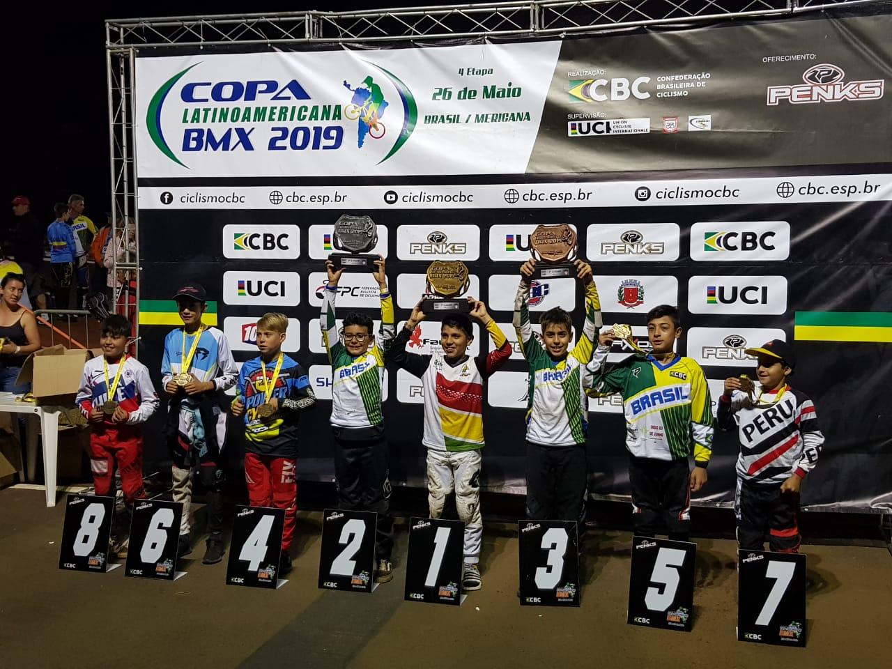 Atletas seguram troféus com a numeração do pódio à frente de cada competidor