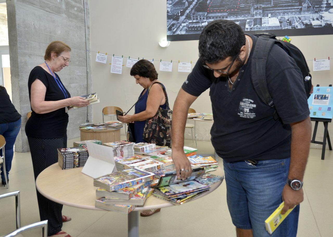 Homem olha e pega livros que estão em cima de uma mesa enquanto duas mulheres olham outros livros