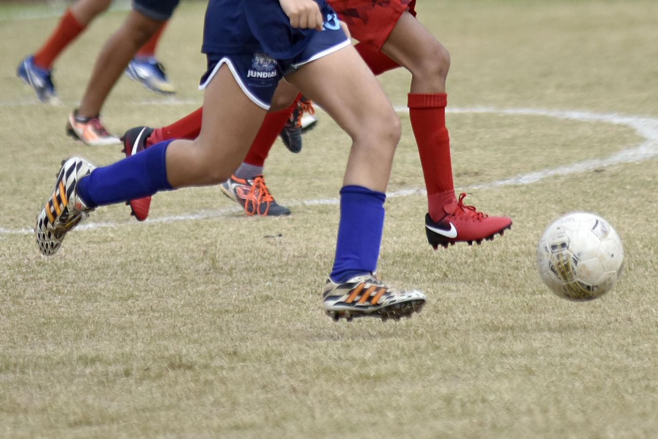 Foto de  pernas de jogadores com a bola de futebol no campo