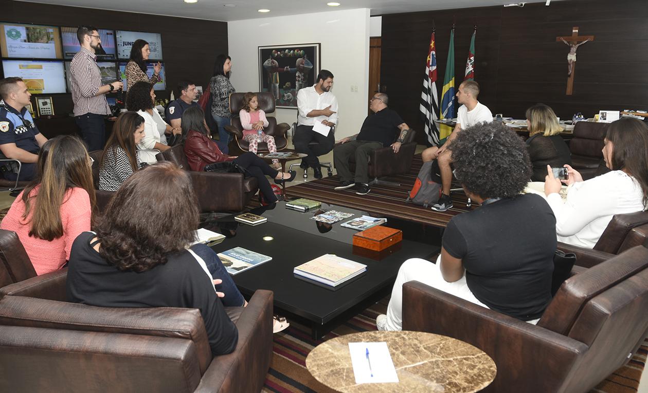 Gabinete de trabalho do prefeito, com alunos sentados em situação de reunião e televisores ao fundo