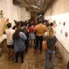 Galeria de Arte, com mostra e expectadores no corredor